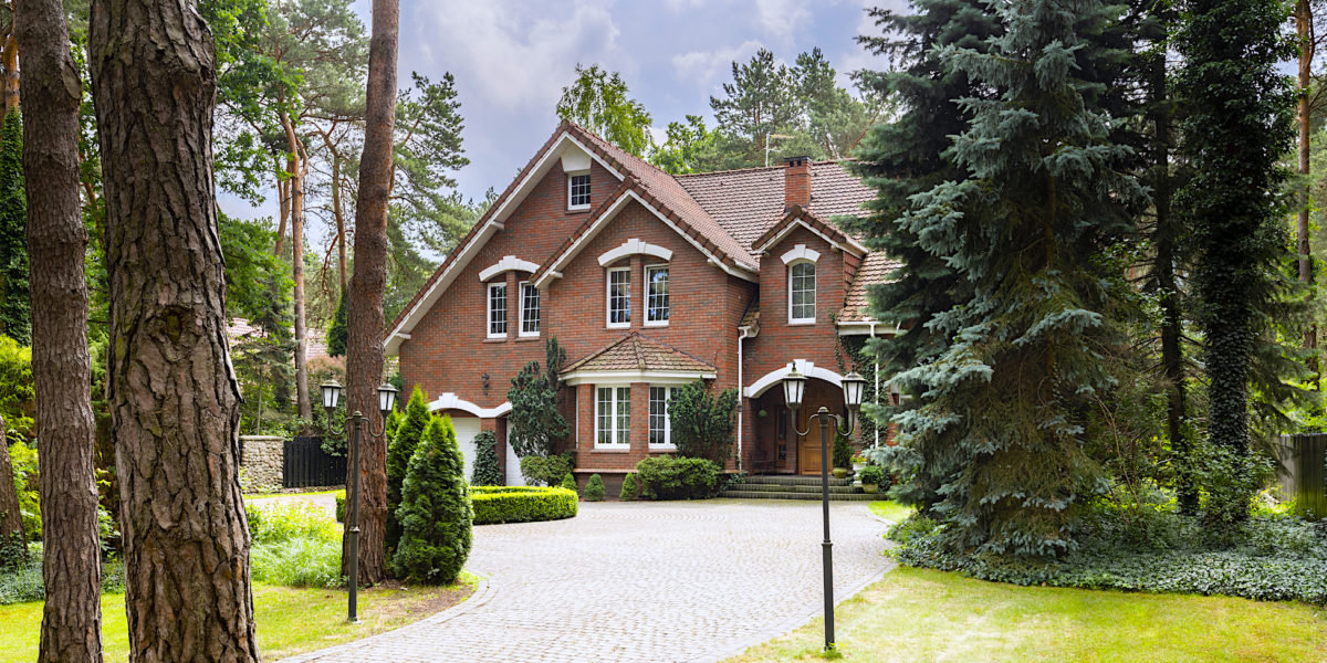Large, rural estate with brick facade and green lawn standing in the forest among trees